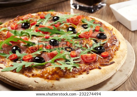 Pizza peperoni on plate with black olives, rocket and mozzarella cheese - stock photo