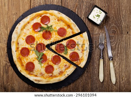 Pizza peperoni on stone black try with rocket and mozzarella cheese - stock photo