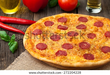 Pizza pepperoni unsliced traditional food on vintage background. Served with tomatoes, pepper, and beer - stock photo