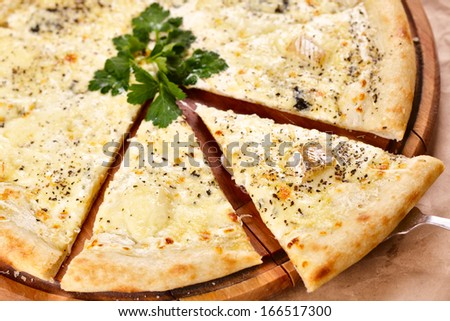 Pizza quattro fromaggi on a wooden board - stock photo