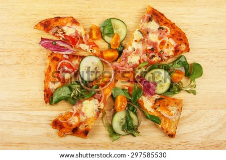 Pizza slices and dressed salad on a wooden board - stock photo