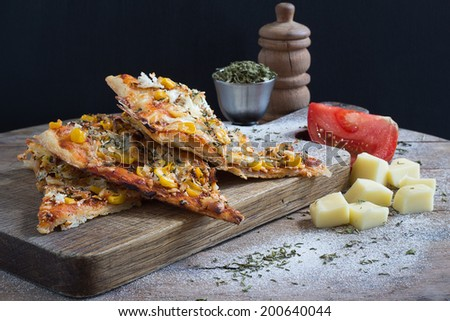 Pizza Slices on a Wooden Cutting Board - stock photo