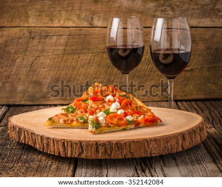 Pizza slices served with glasses of red wine. - stock photo