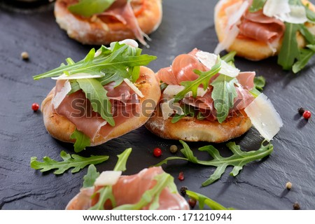 Pizza snacks with parma ham, rucola leaves and parmesan cheese - stock photo