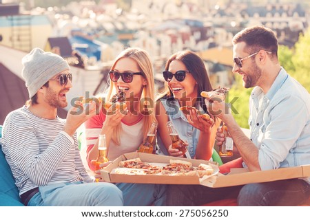 Pizza time. Four young happy people eating pizza and drinking beer while sitting at the bean bags on the roof of the building - stock photo