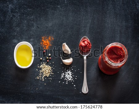 Pizza topping sauce ingredients or recipe on black background. Tomato puree, olive oil, garlic, oregano, salt and pepper from above - cooking food. Background with free text space. - stock photo