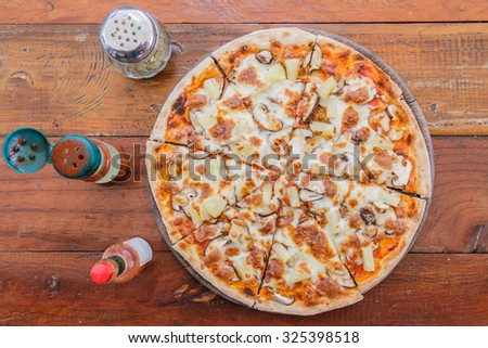 Pizza vegetarian with mushroom and pineapple on wood table in restaurant. top view. - stock photo
