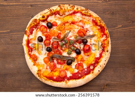 Pizza with anchovies and olives on a wooden table top view
