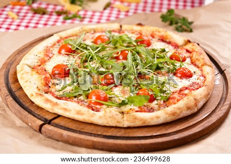Pizza with arugula and cherry tomatoes on wooden board - stock photo