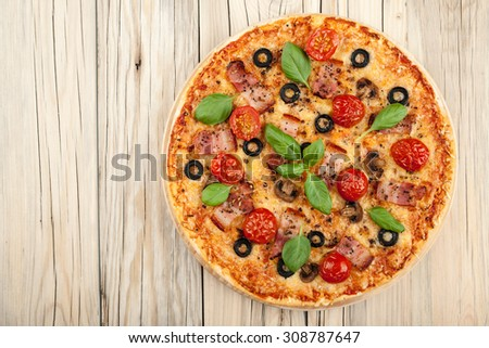 Pizza with bacon and mushrooms on cutting board on wooden background