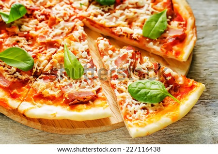 pizza with bacon, mozzarella and spinach in a light woody background. tinting. selective focus