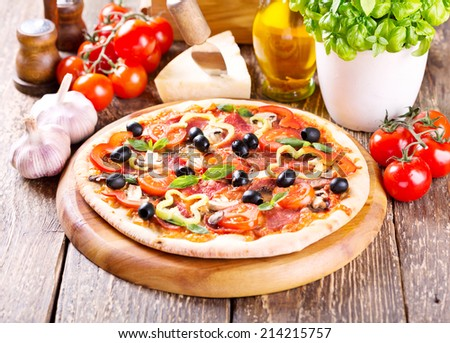 pizza with bacon, vegetables and olives on wooden table