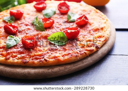 Pizza with basil and cherry tomatoes on wooden cutting board, closeup