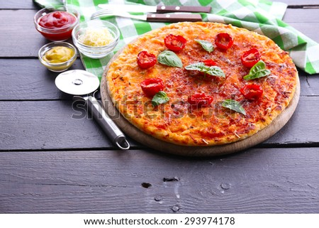 Pizza with basil and cherry tomatoes on wooden table, closeup