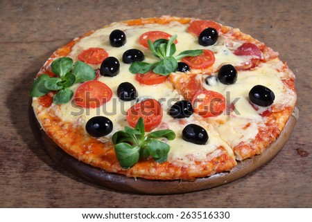 Pizza with cheese, a salami, tomatoes, olives and Rucola - stock photo
