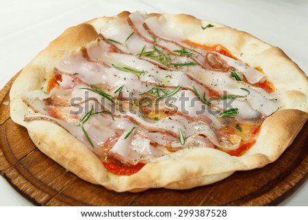 Pizza with cheese, bacon and rosemary - stock photo