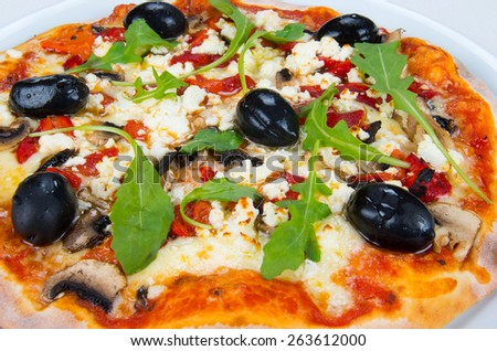 Pizza with cheese, mushrooms, peppers, tomato sauce, arugula and olives.