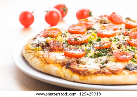 Pizza with cherry tomatoes and dry basil on the ceramic white plate closeup - stock photo