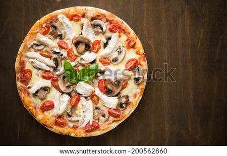 Pizza with chicken and mushrooms on dark wooden background top view - stock photo