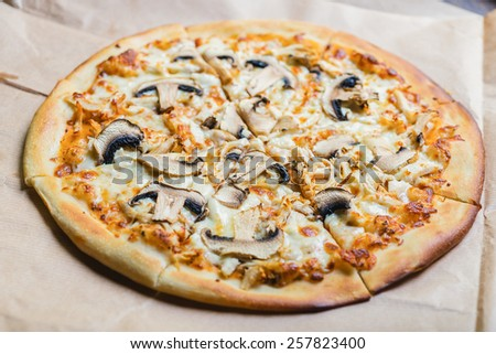 Pizza with chicken and mushrooms on paper background on the wooden table with decor - stock photo