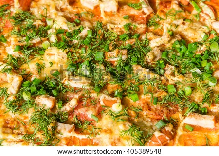Pizza with chicken, onion, cheese and greens as background or texture of food. - stock photo