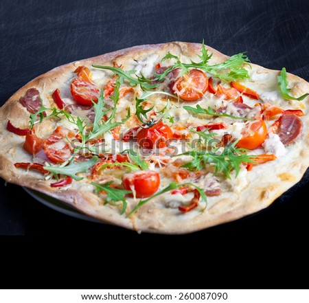 Pizza with dry cured ham and arugula - stock photo