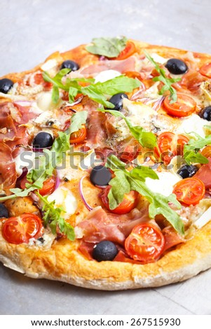 Pizza with dry cured ham and basil