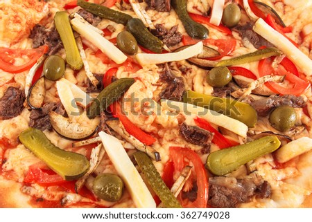 Pizza with eggplant, beef, tomato, cucumber, green olives, and cheese close-up, selective focus, macro - stock photo
