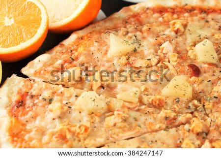 Pizza with exotic fruit and chicken close-up. Shallow depth of field