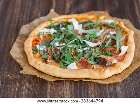 Pizza with figs, prosciutto,cheese and arugula.selective focus - stock photo