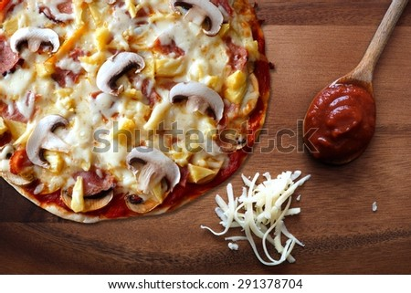 Pizza with ham, mushroom and pineapple against a wood background with shredded mozzarella cheese and spoon of tomato sauce - stock photo