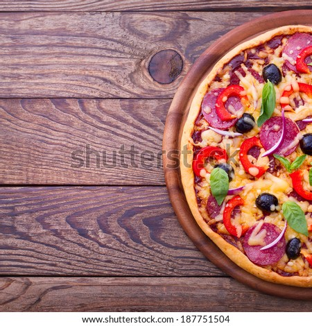 Pizza with ham, pepper and olives. Delicious fresh pizza served on wooden table. Pizza with tomato, salami and olives  - stock photo