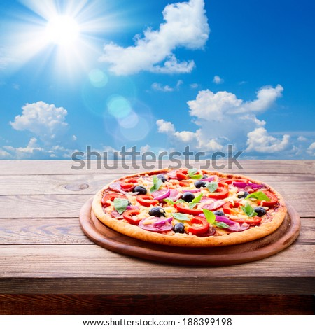 Pizza with ham, pepper and olives. Delicious fresh pizza served on wooden table. Pizza with tomato, salami and olives on background of blue sunny sky  - stock photo