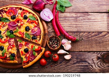 Pizza with ham, pepper and olives. Delicious fresh pizza served on wooden table. Pizza with tomato, salami and olives. Ingredient.