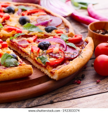 Pizza with ham, pepper and olives. Delicious fresh pizza served on wooden table. Pizza with tomato, salami and olives. Ingredient.  - stock photo