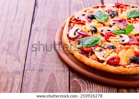 Pizza with ham, pepper, mushrooms and olives. Delicious fresh pizza served on wooden table. Pizza with tomato, salami and olives  - stock photo