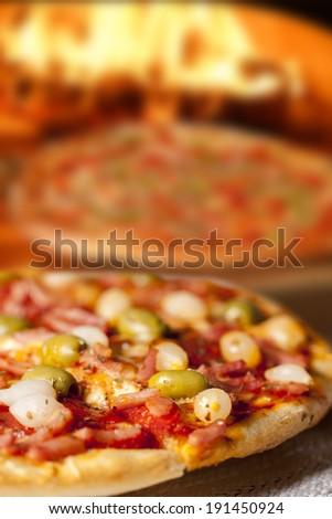 Pizza with ham, salami, olive, bacon, onion - stock photo