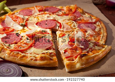 Pizza with Ham, Salami, Tomatoes and Mozzarella Cheese - stock photo
