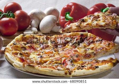 Pizza with ingredients on the table a slice is lifted with the hand