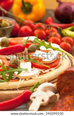 Pizza with ingredients, ready for baking - stock photo