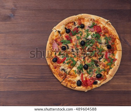 Pizza with mashrooms and chiken and olives on a wooden board