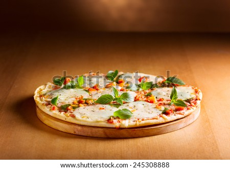 pizza with mozzarella and green basil on wooden background - stock photo