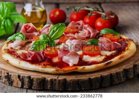 pizza with mozzarella and prosciutto, tomatoes - stock photo