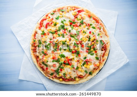 Pizza with mozzarella cheese, chicken, sweet corn, sweet pepper and parsley on blue wooden background top view. Italian cuisine. - stock photo