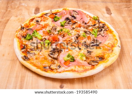 pizza with mozzarella,  ham, mushrooms chicken, broccoli, and tomatoes, whole, uncut, on wooden table - stock photo
