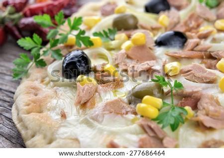 Pizza with mozzarella,tuna,corn,onions and olives - stock photo