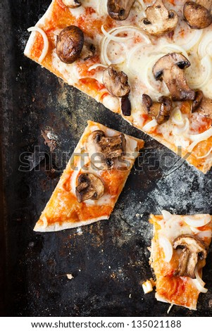 pizza with mushrooms and mozzarella cheese on a baking tray, closeup - stock photo