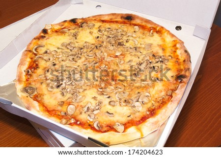 Pizza with mushrooms, cheese and ketchup in a delivery box.