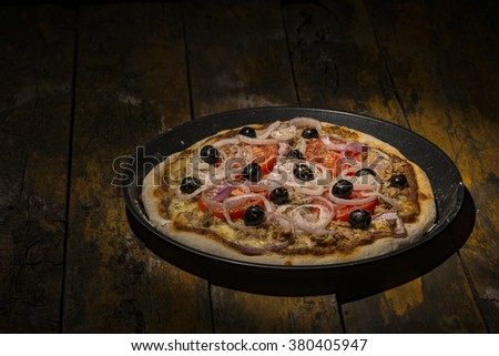 pizza with onions, tuna, tomatoes and olives on wooden table