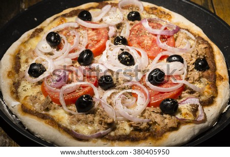 pizza with onions, tuna, tomatoes and olives on wooden table - stock photo